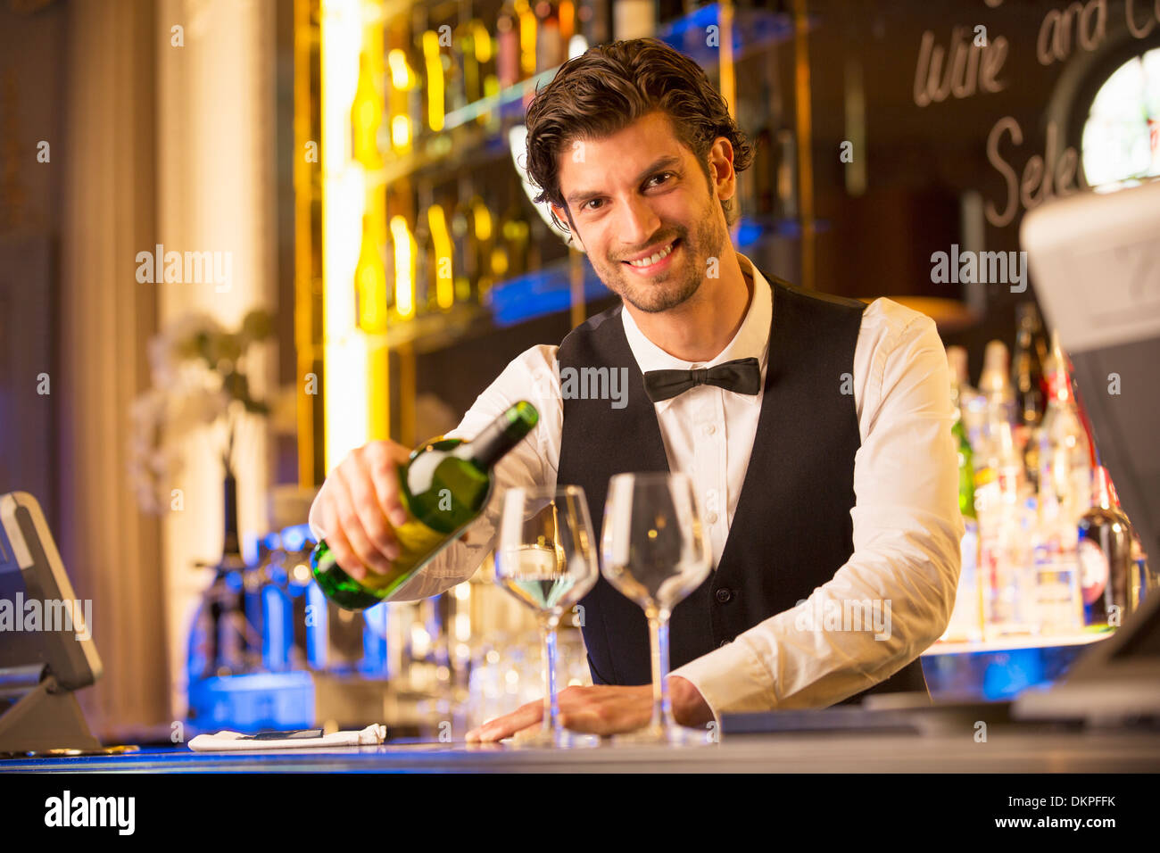 Portrait of well dressed bartender pouring wine in luxury bar - Stock Image