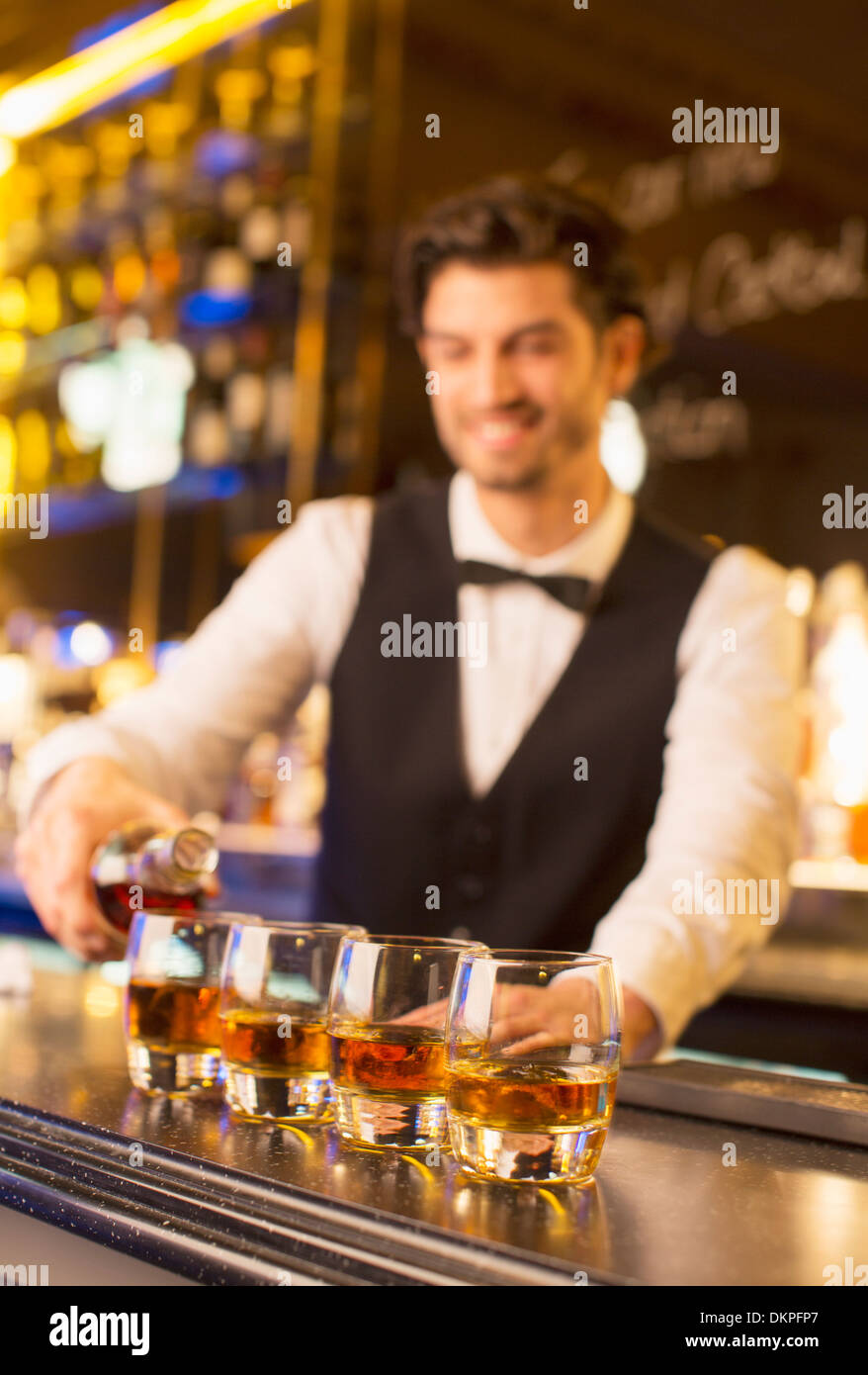 Well dressed bartender pouring bourbon in luxury bar - Stock Image