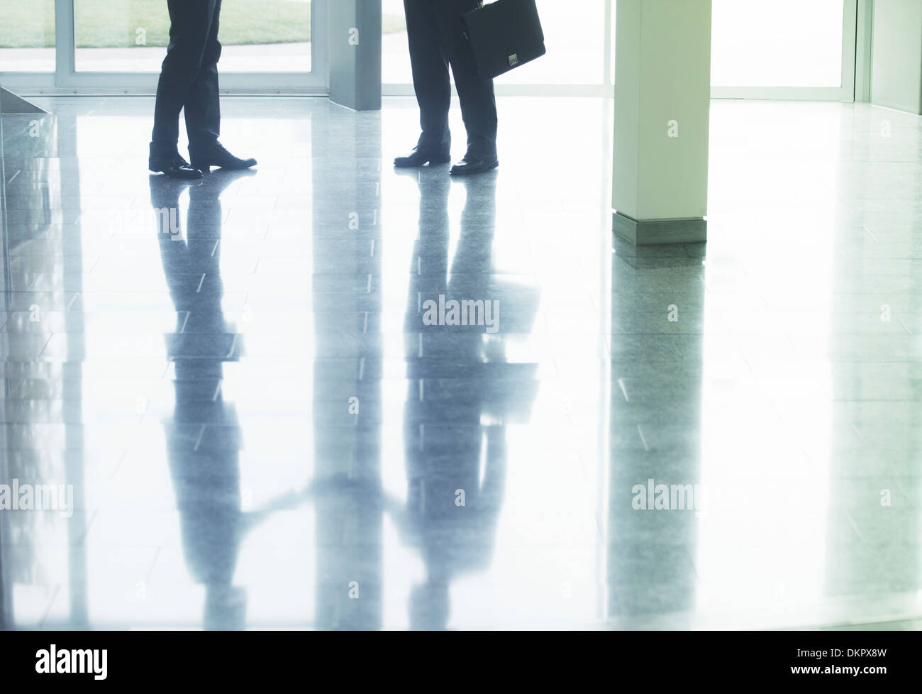 Reflection of businessmen shaking hands in office lobby - Stock Image