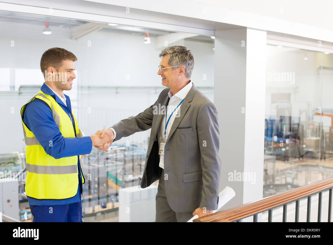 Supervisor and worker shaking hands in factory - Stock Image
