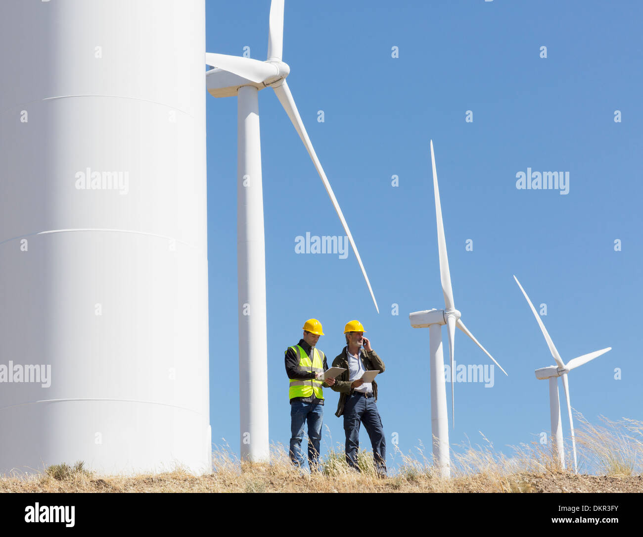 Workers talking by wind turbines in rural landscape Stock Photo