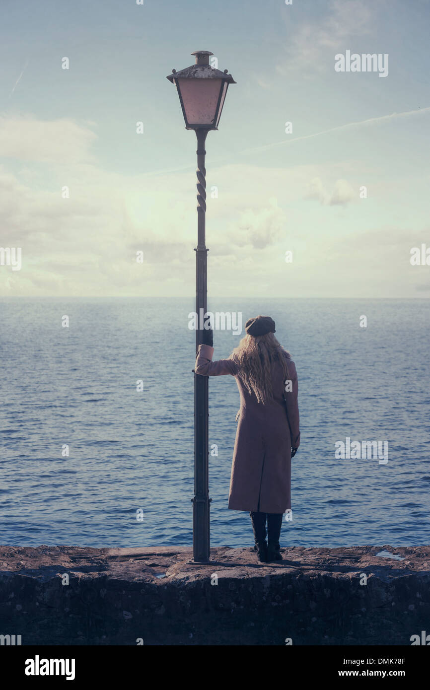 a woman in a pink coat is standing next to a lantern at the sea - Stock Image