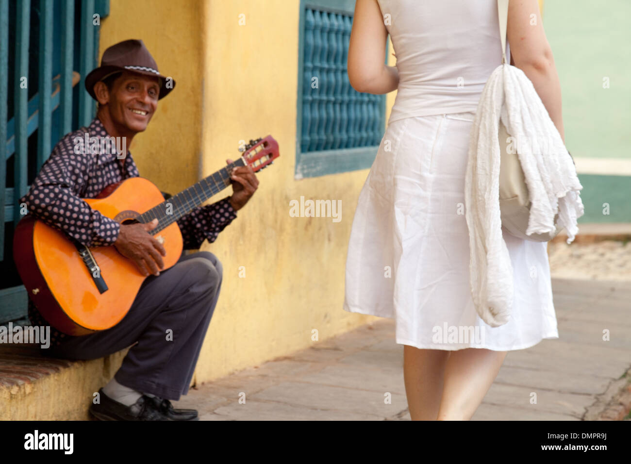 a-guitarist-playing-in-this-street-scene-as-a-woman-walks-past-cuban-DMPR9J.jpg