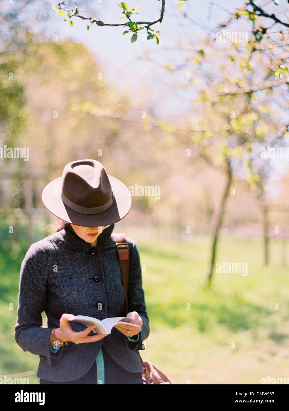 A woman in a hat reading a book. - Stock Image