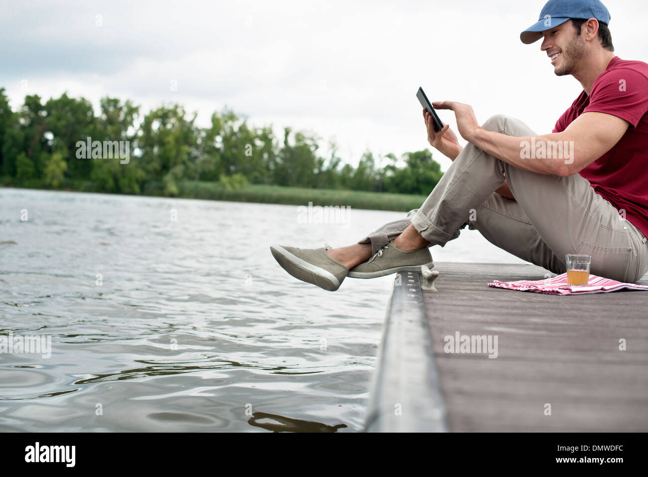 A man seated on a jetty by a lake using a digital tablet. - Stock Image