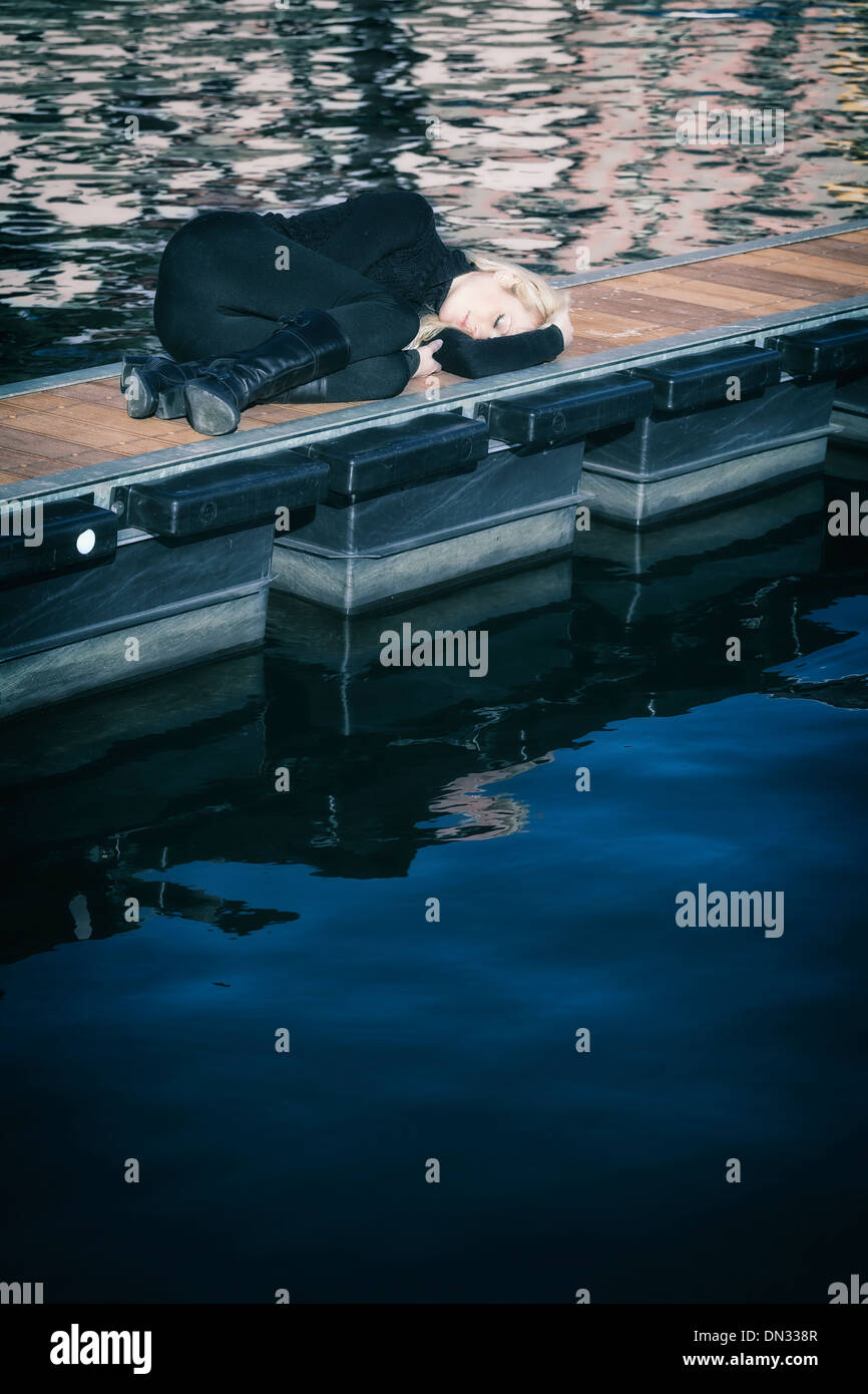 a woman in black clothes is lying on a jetty - Stock Image