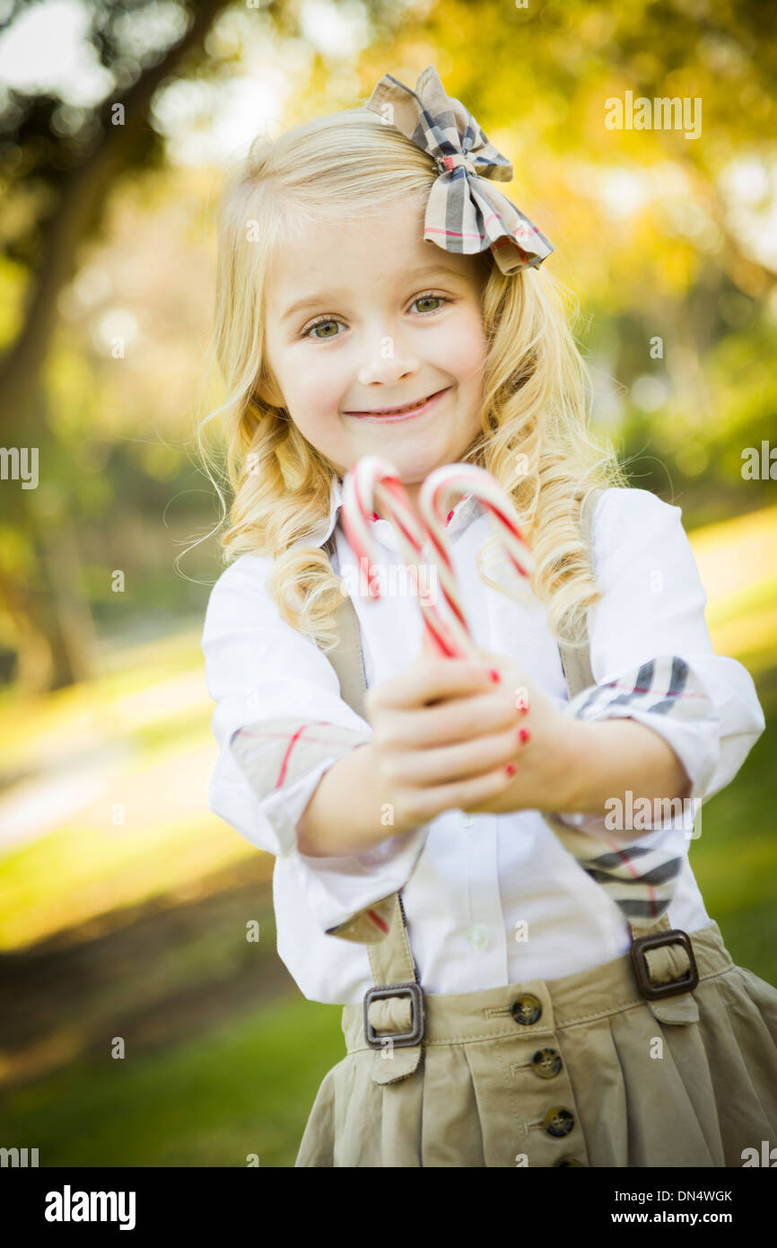 Cute Little Girl with a Bow in Her Hair Holding Her Christmas Candy Canes Outdoors. - Stock Image