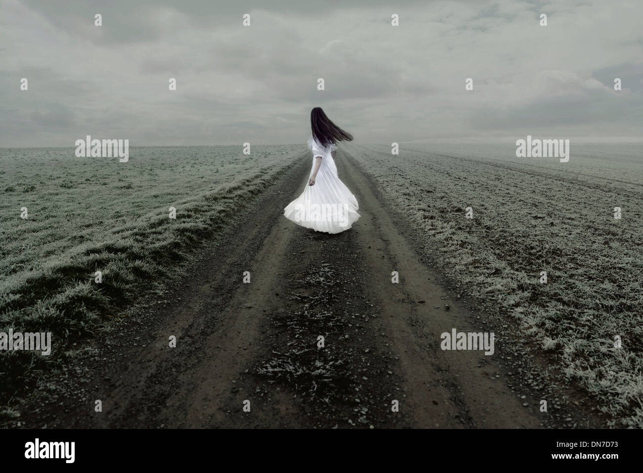 Woman in white dress stands alone on a dirt road - Stock Image