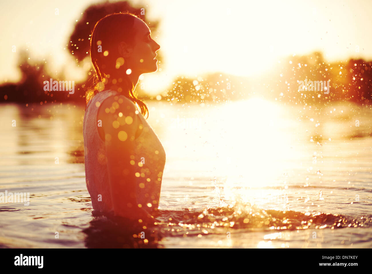 Young woman at sunset in a lake splashing with water - Stock Image