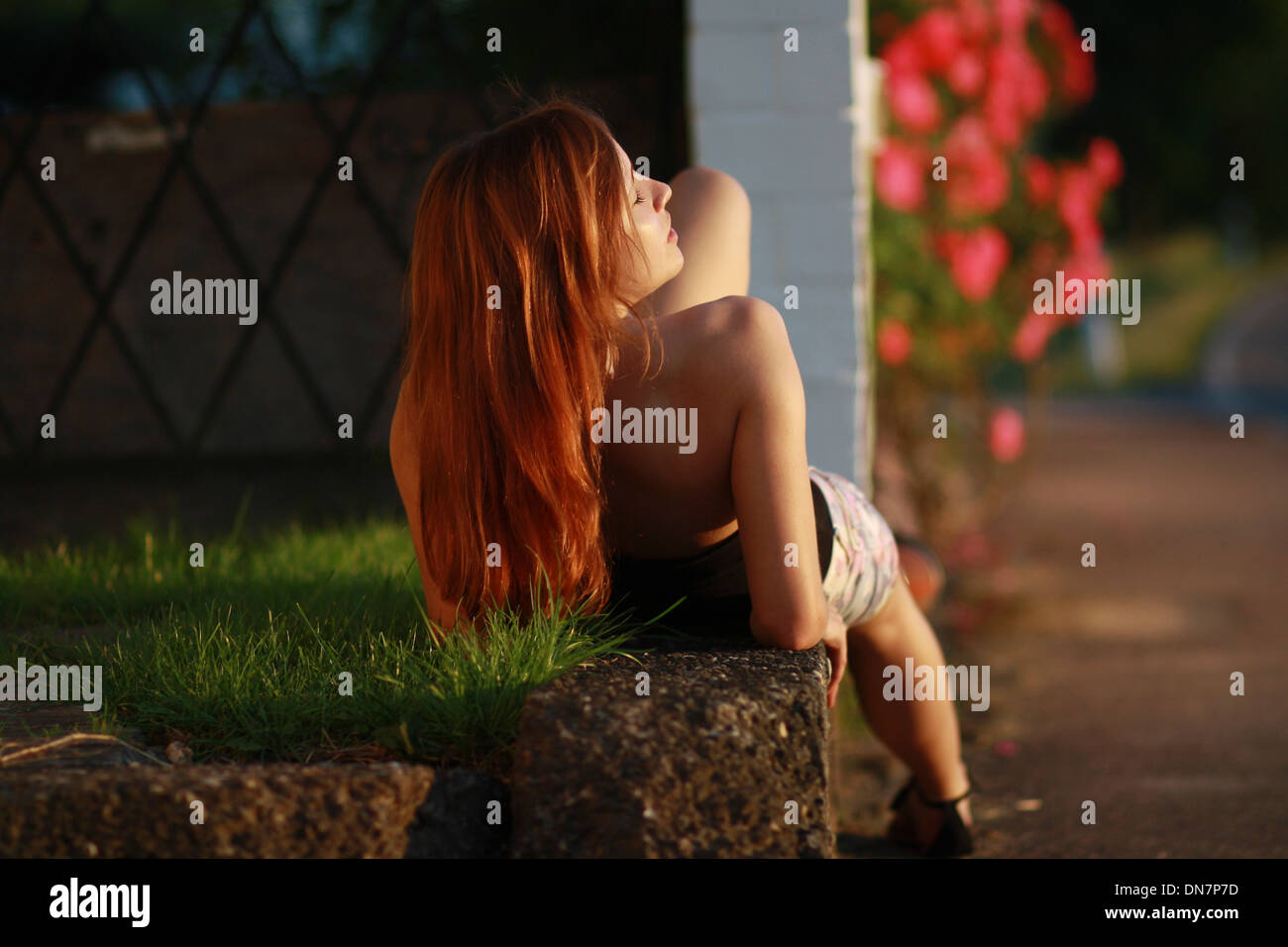 Young woman lying on a brick wall in the sunlight - Stock Image