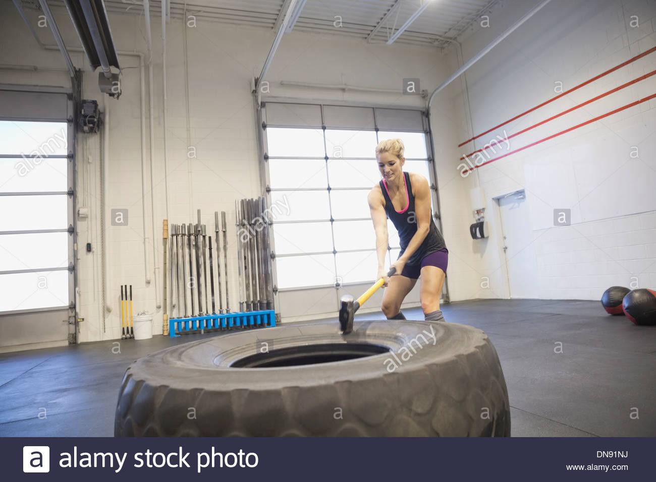 Female athlete hammering truck tire - Stock Image