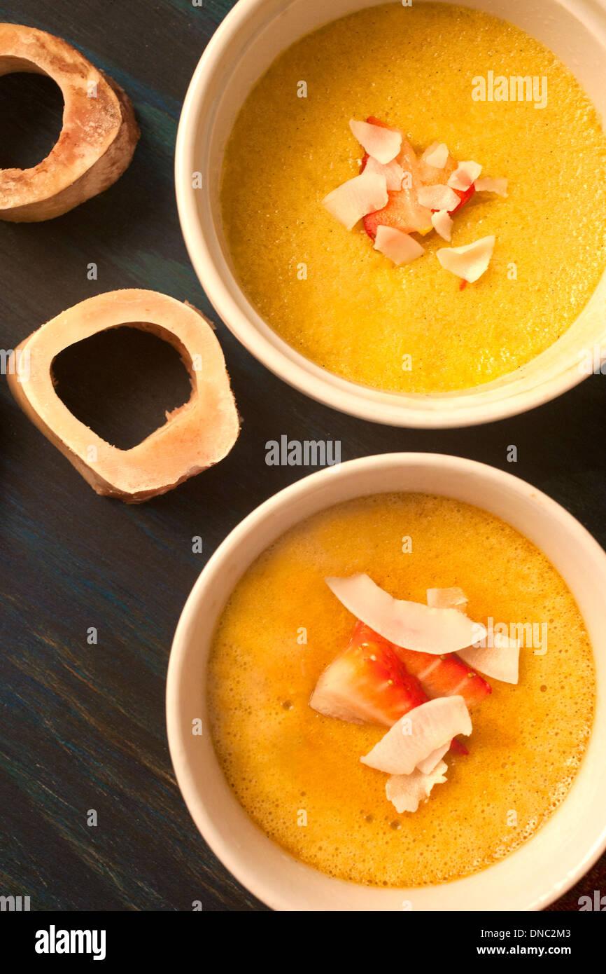 Yellow custard in white souffle dishes overhead Stock Photo