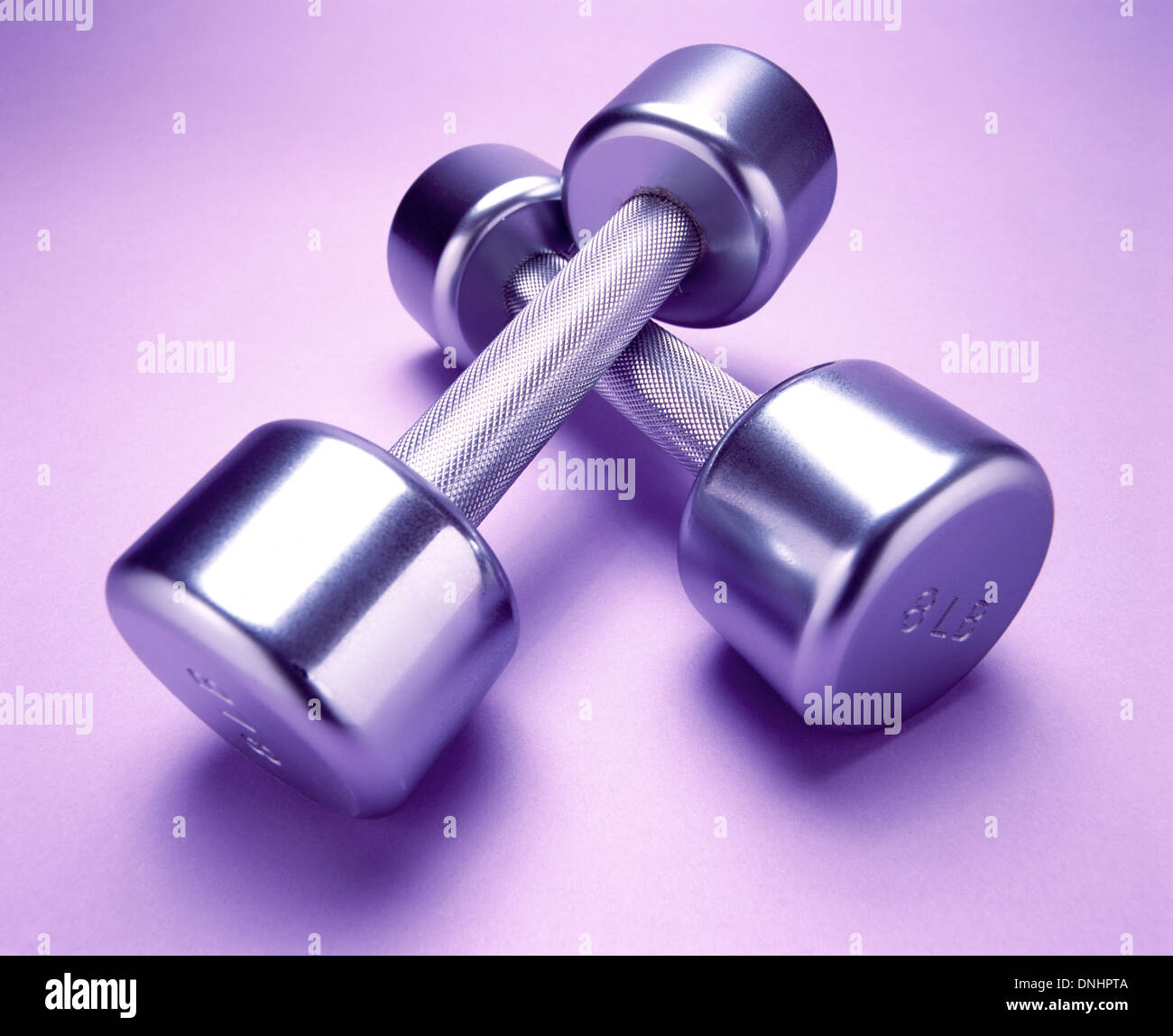 A pair of exercise metal free weights on a light purple exercise mat. - Stock Image