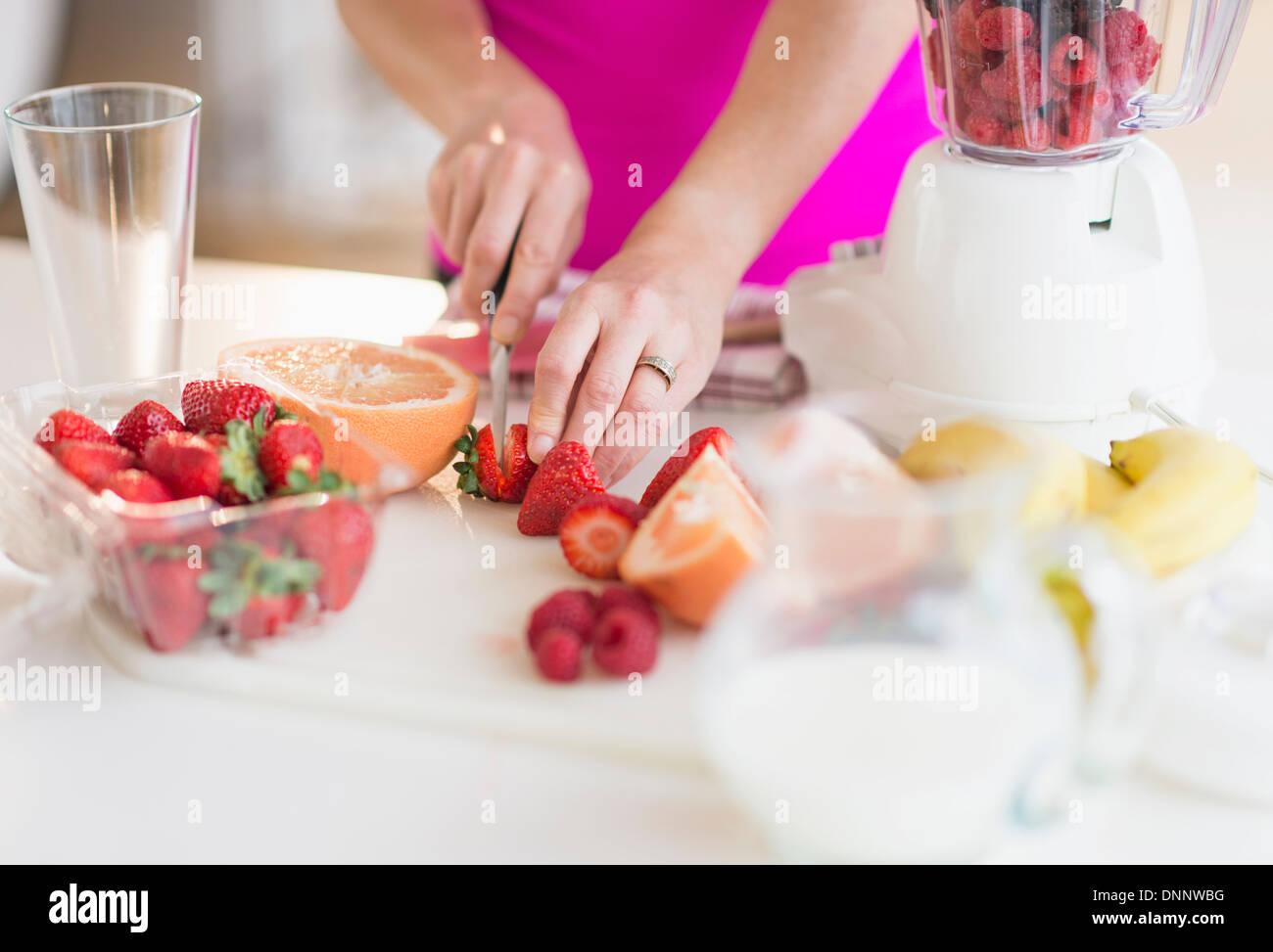 Woman slicing strawberries - Stock Image