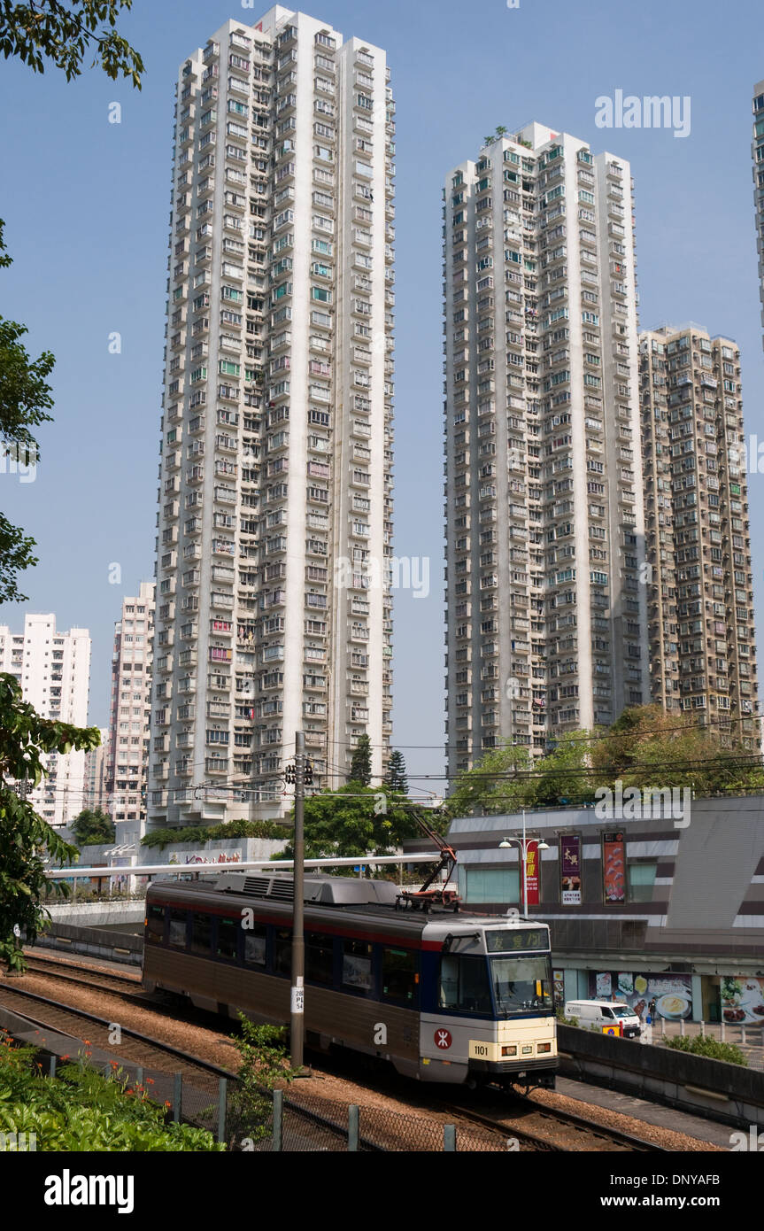 A Mass Transit Rail tram passes tall housing apartment's in the new territories town of Tuen Mun, Hong Kong - Stock Image