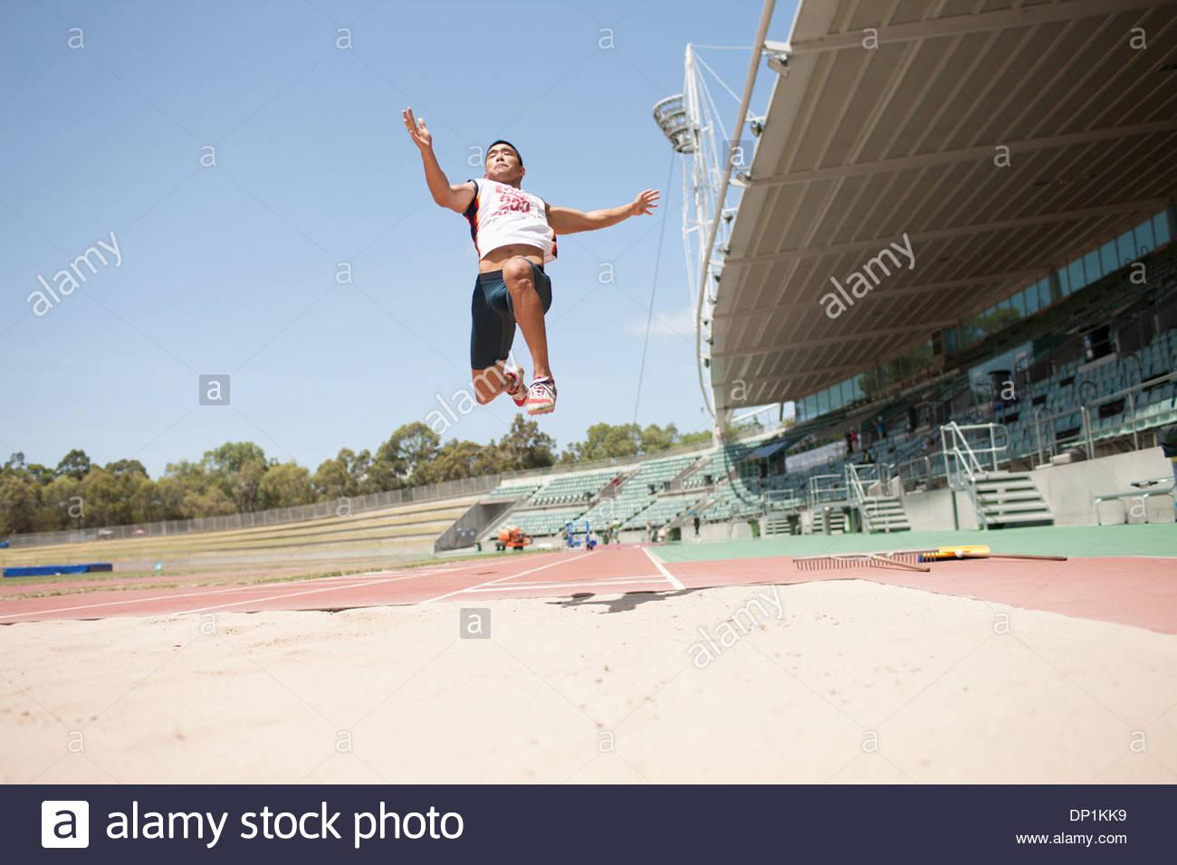 Runner doing long jump - Stock Image