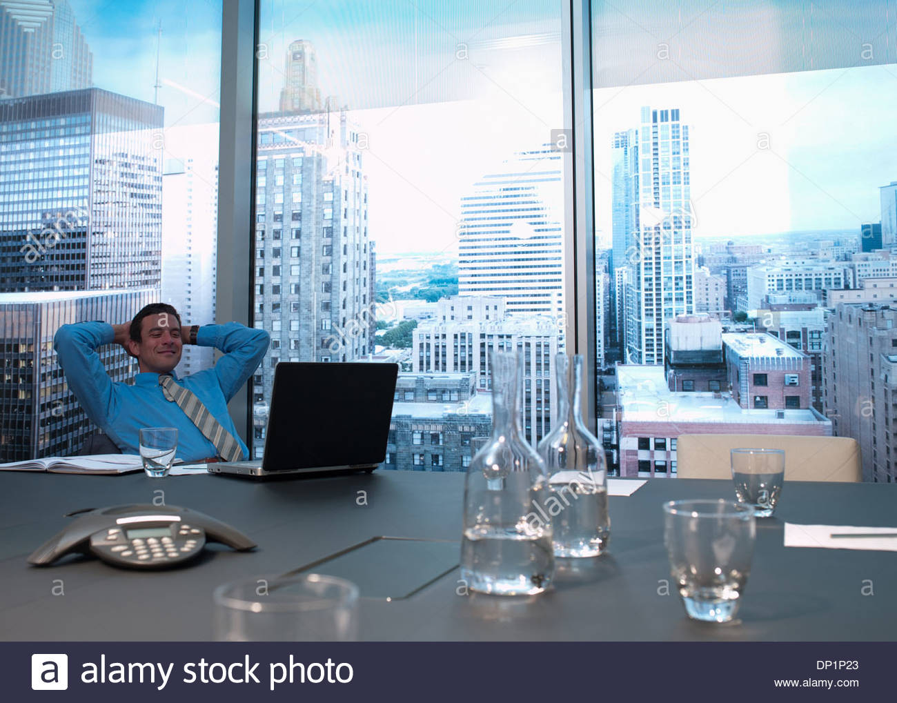 Smiling businessman with hands behind head in conference room - Stock Image
