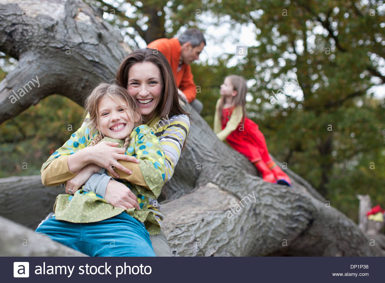 Family climbing on tree branch - Stock Image