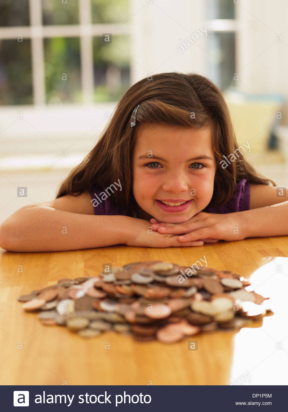 Smiling girl looking at pile of coins - Stock Image