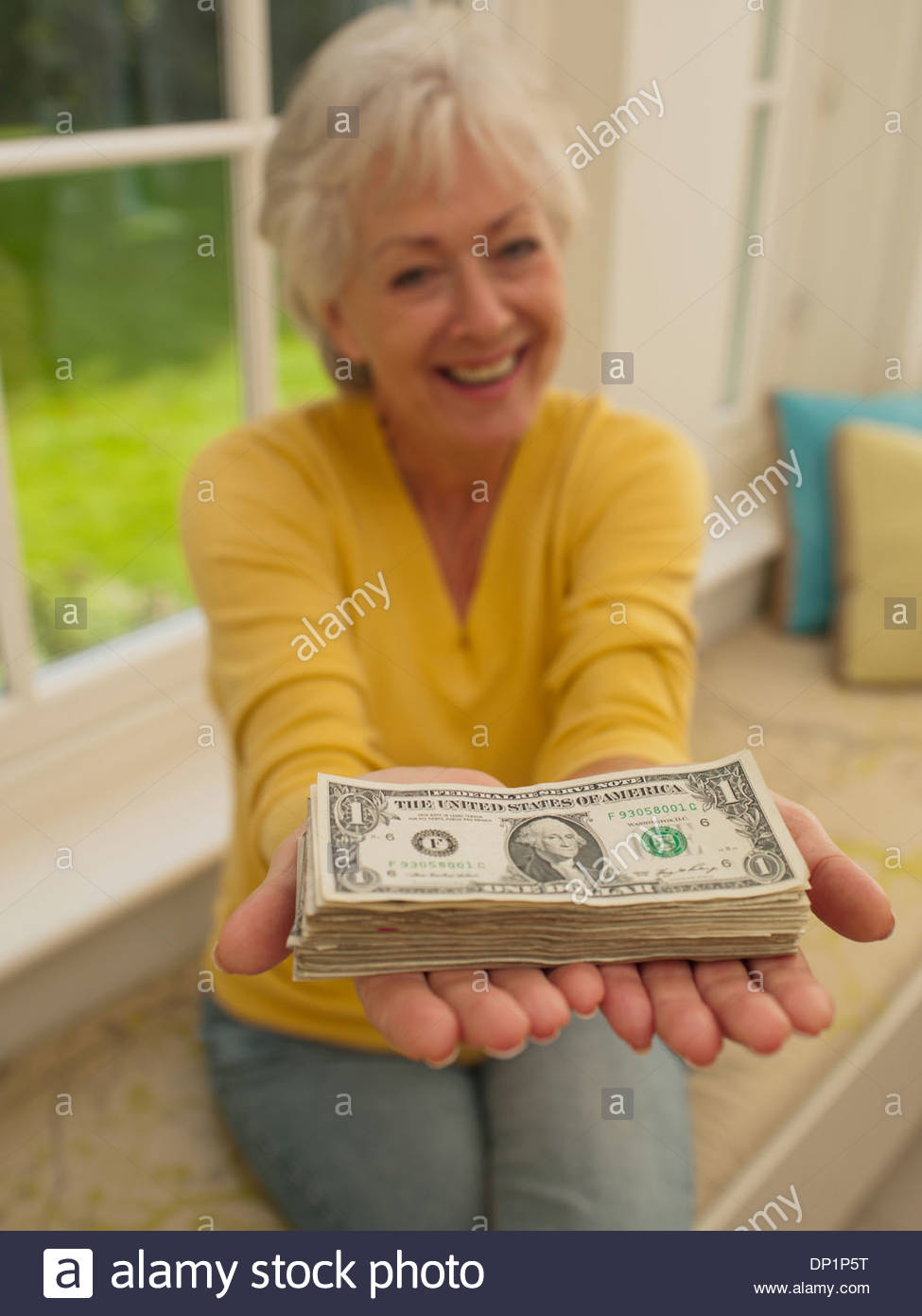 Woman holding out stack of one dollar bills - Stock Image