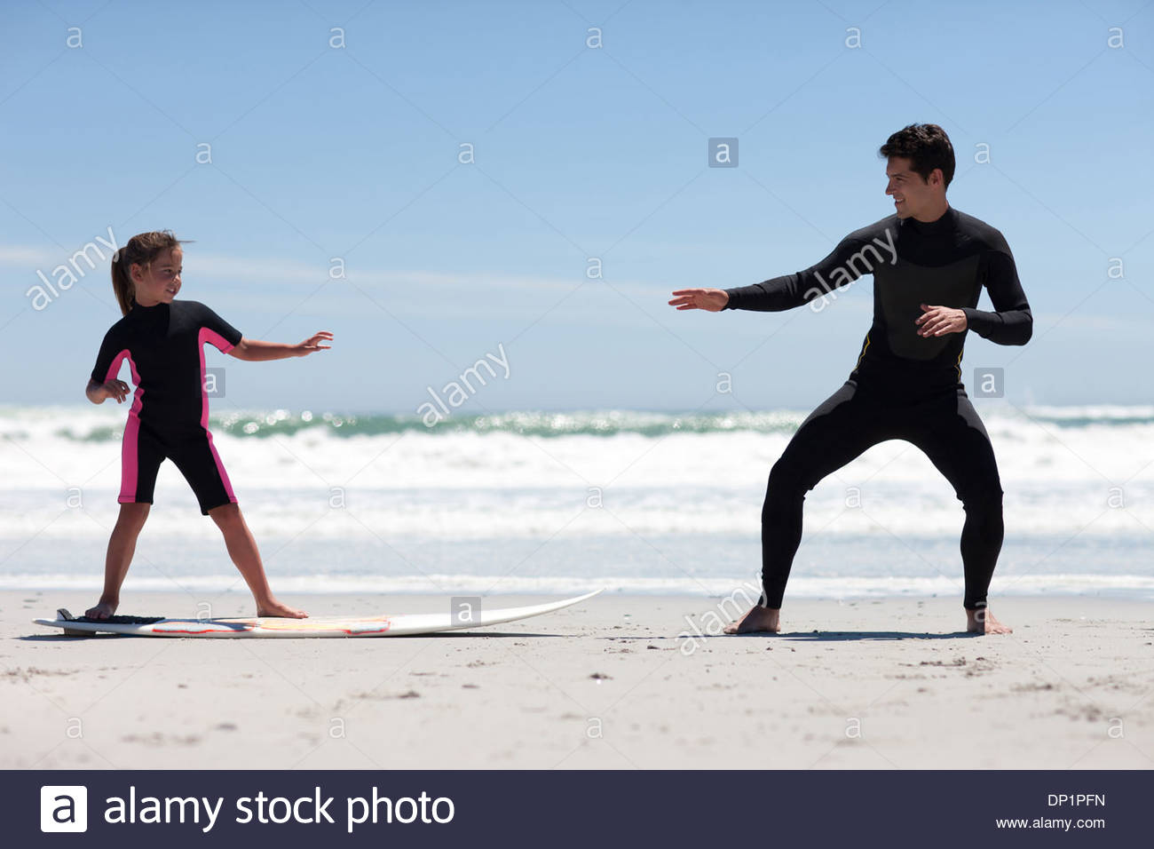 Father teaching daughter to surf - Stock Image