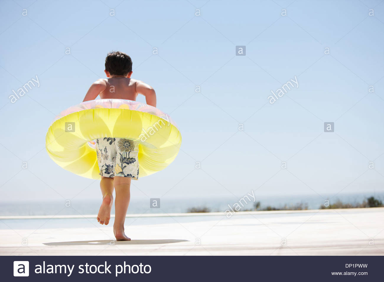 Boy with inflatable ring stepping out of infinity pool - Stock Image