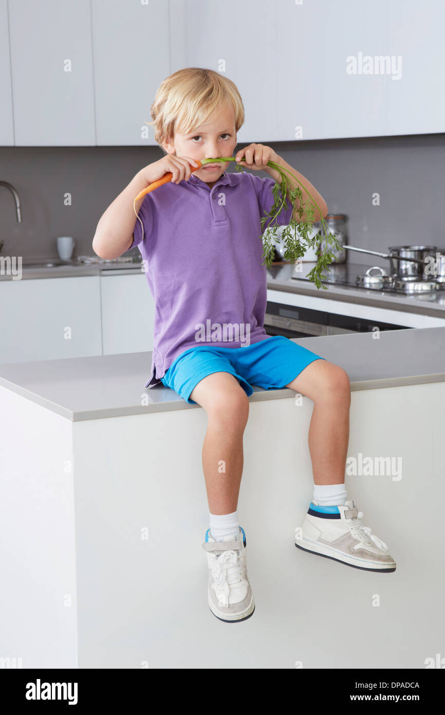 Boy sitting on side in kitchen with carrot moustache - Stock Image