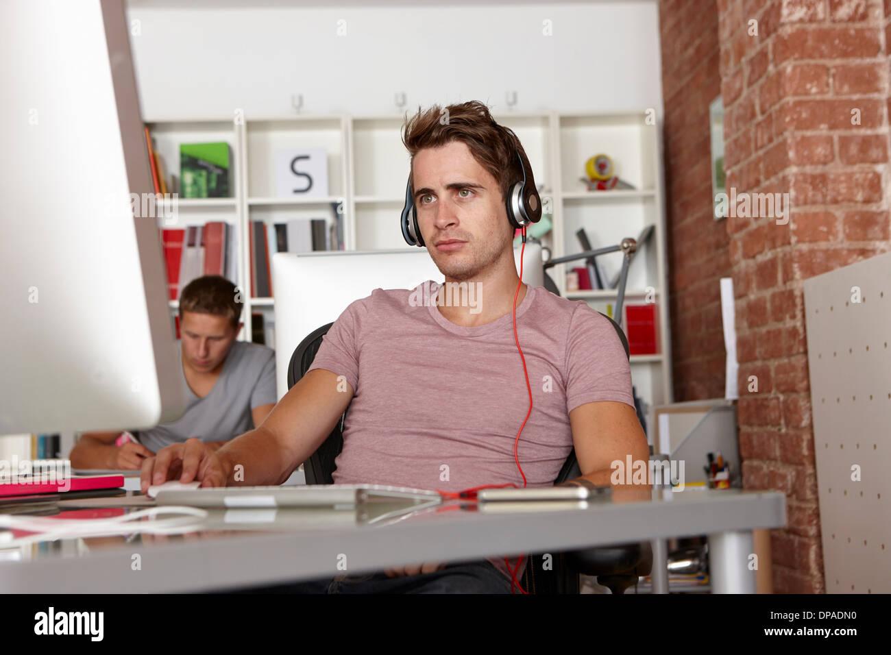Young man at work wearing headphones - Stock Image