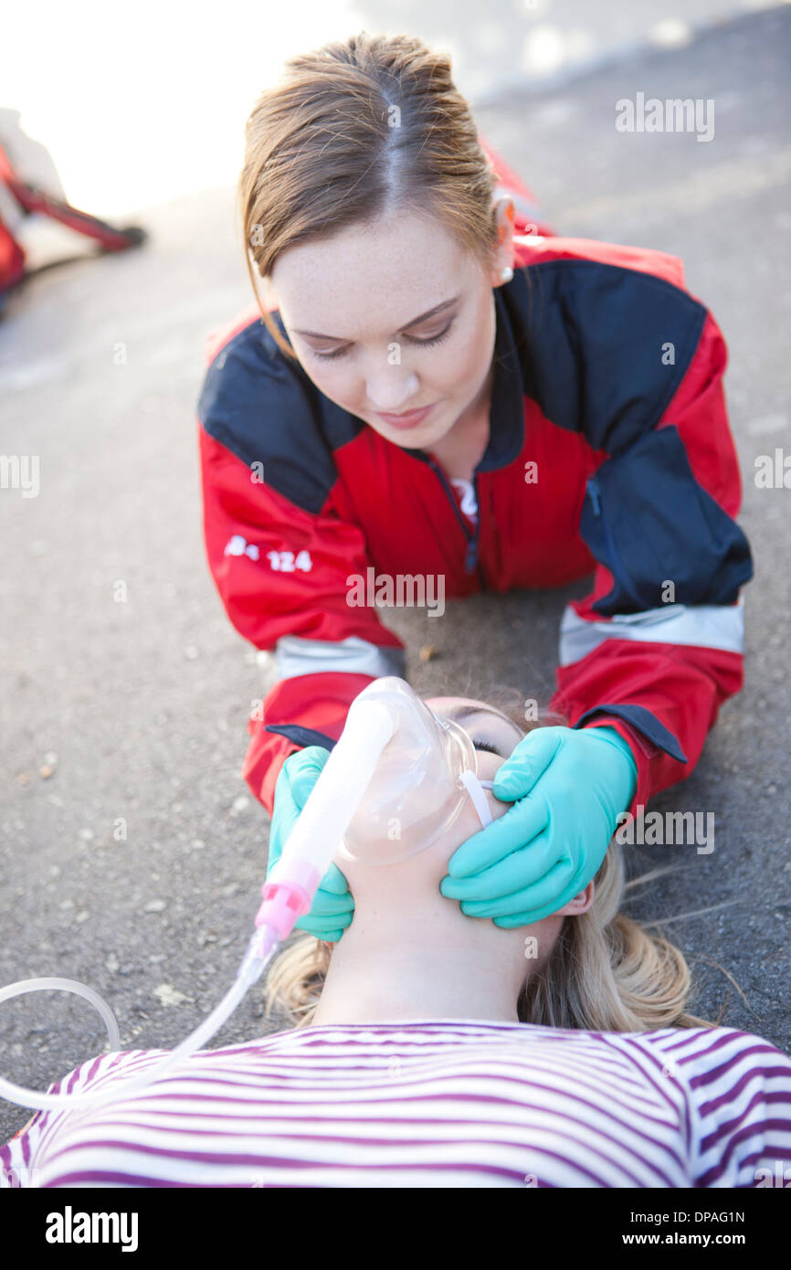 Female paramedic tending patient on road - Stock Image
