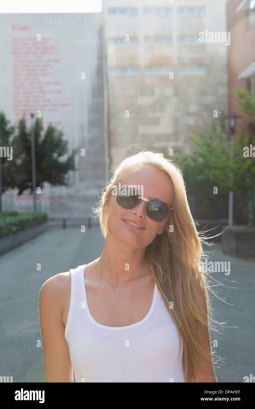 Young woman walking carefree in street - Stock Image