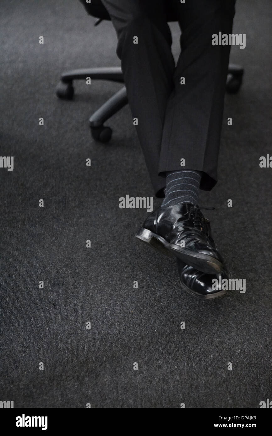 Businessman wearing black shoes and trousers, low section - Stock Image