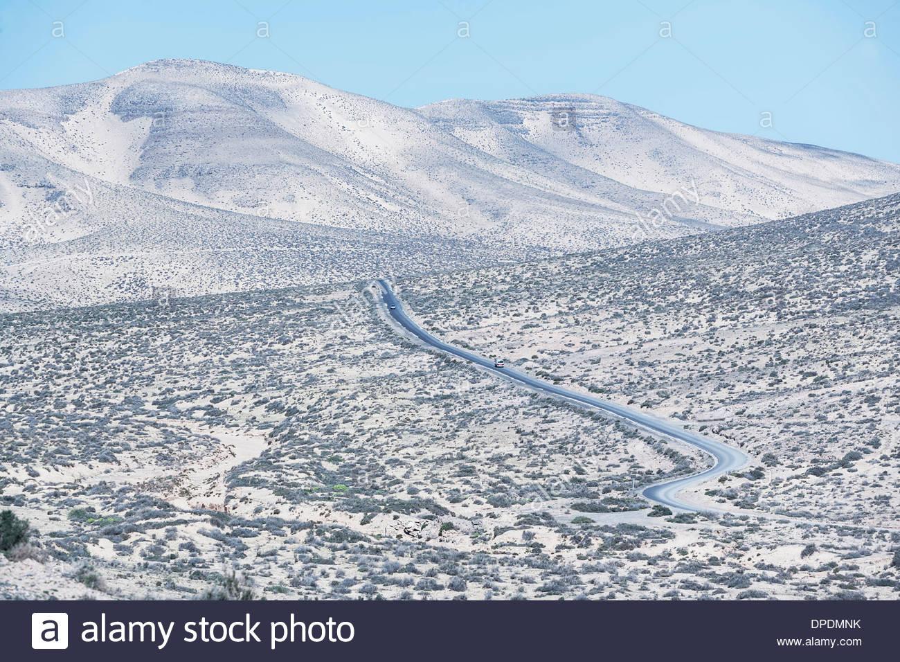Road winding through Fuerteventura landscape, Canary Islands, Spain - Stock Image