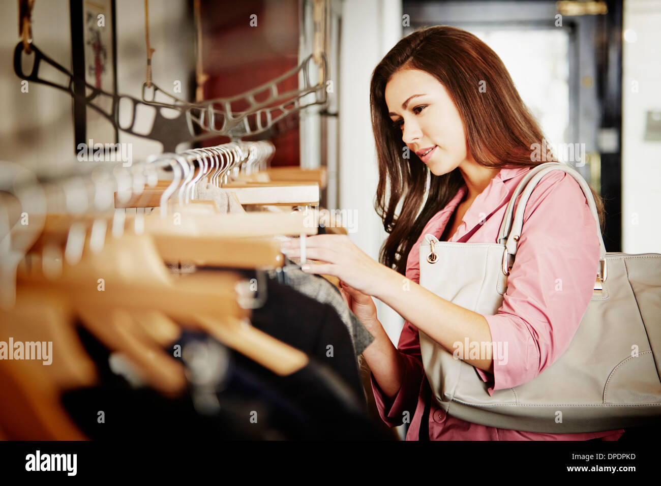 Young woman looking at selection of clothes on clothes rail - Stock Image