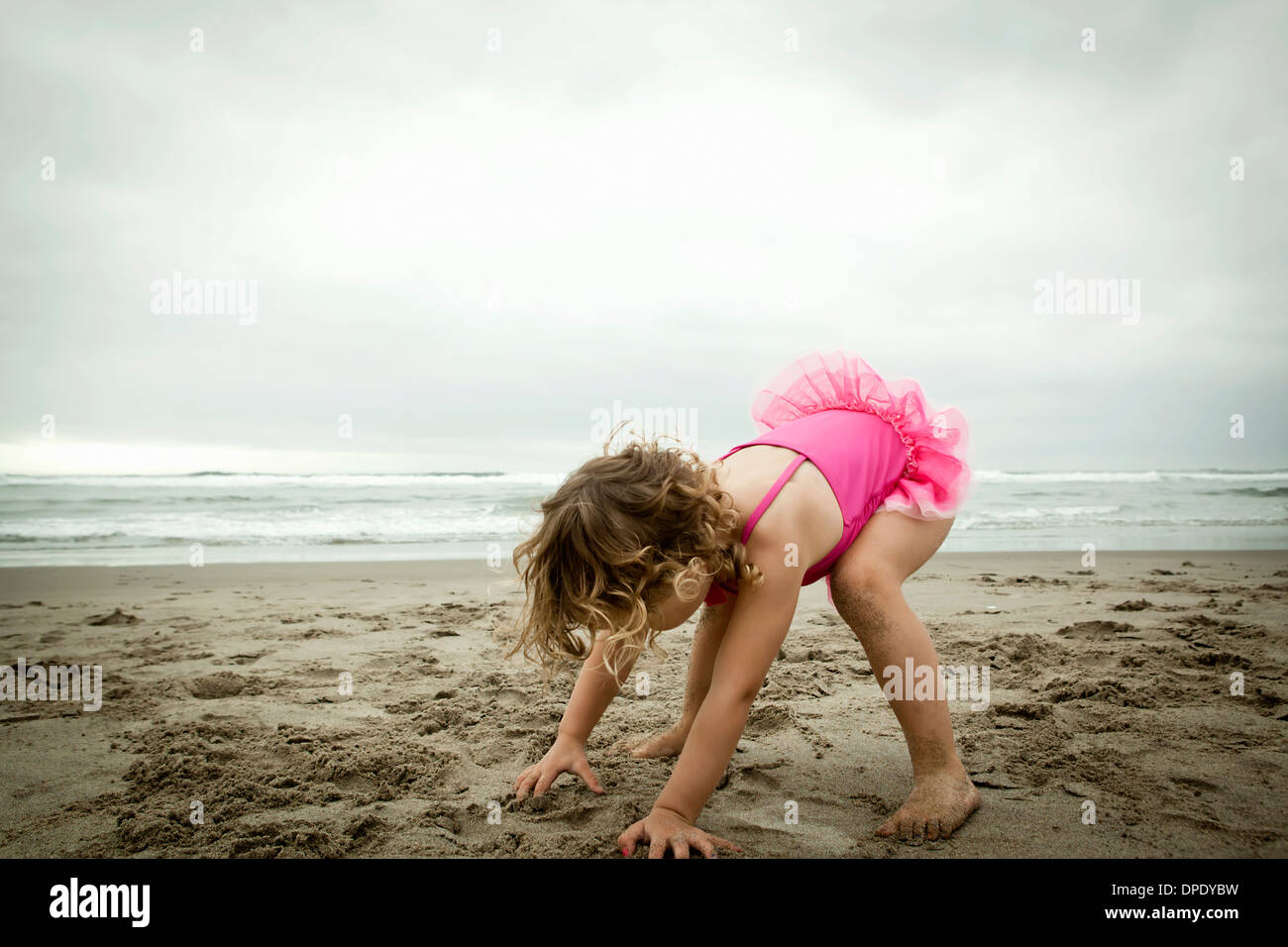 Female toddler playing with sand - Stock Image