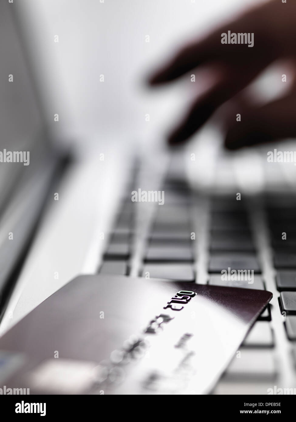 Hand tapping account details on laptop to illustrate internet shopping and internet fraud Stock Photo