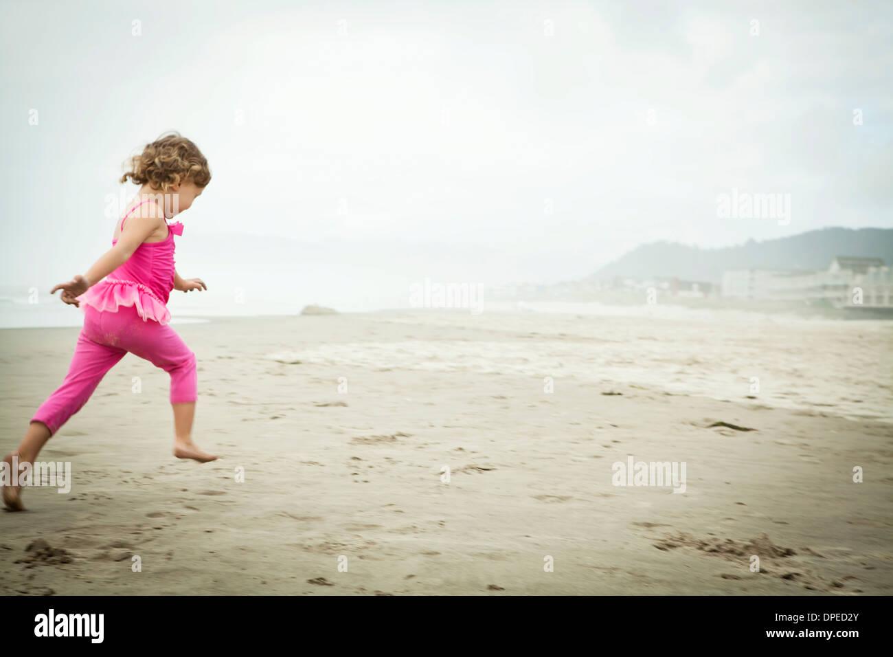 Female toddler running on beach - Stock Image