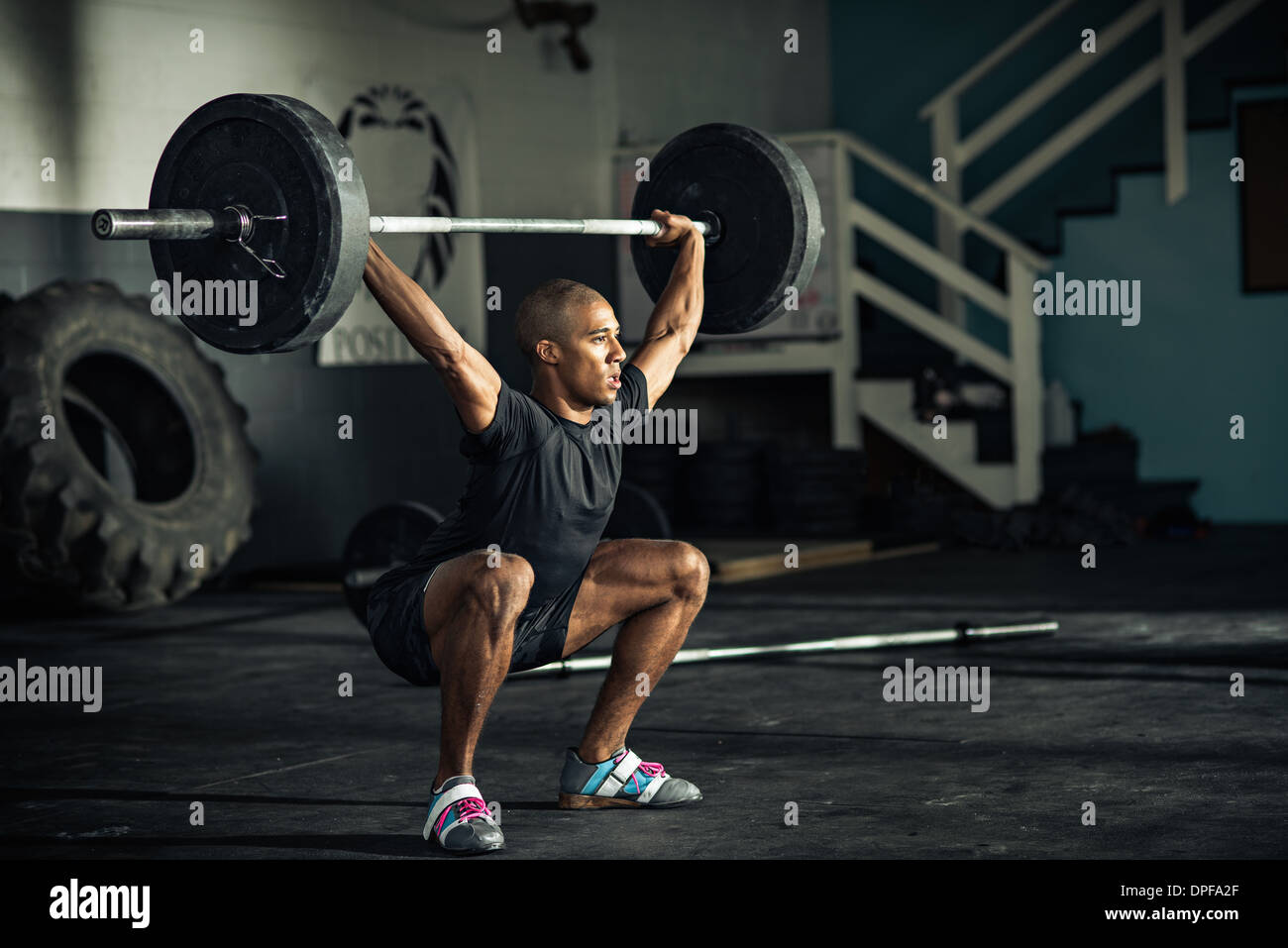 Young man weightlifting barbells in gymnasium - Stock Image
