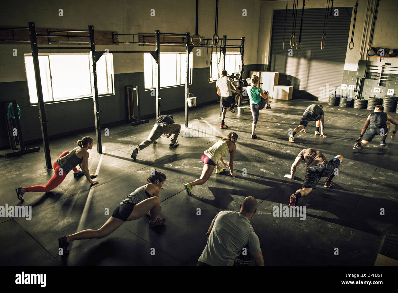 Fitness class training and stretching together in gym - Stock Image