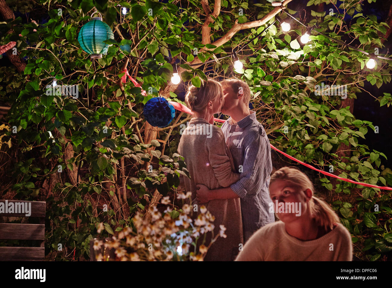 Young couple embracing at garden party at night - Stock Image
