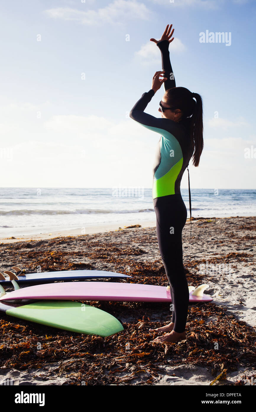 Mid adult woman preparing to surf, Encinitas, California, USA - Stock Image