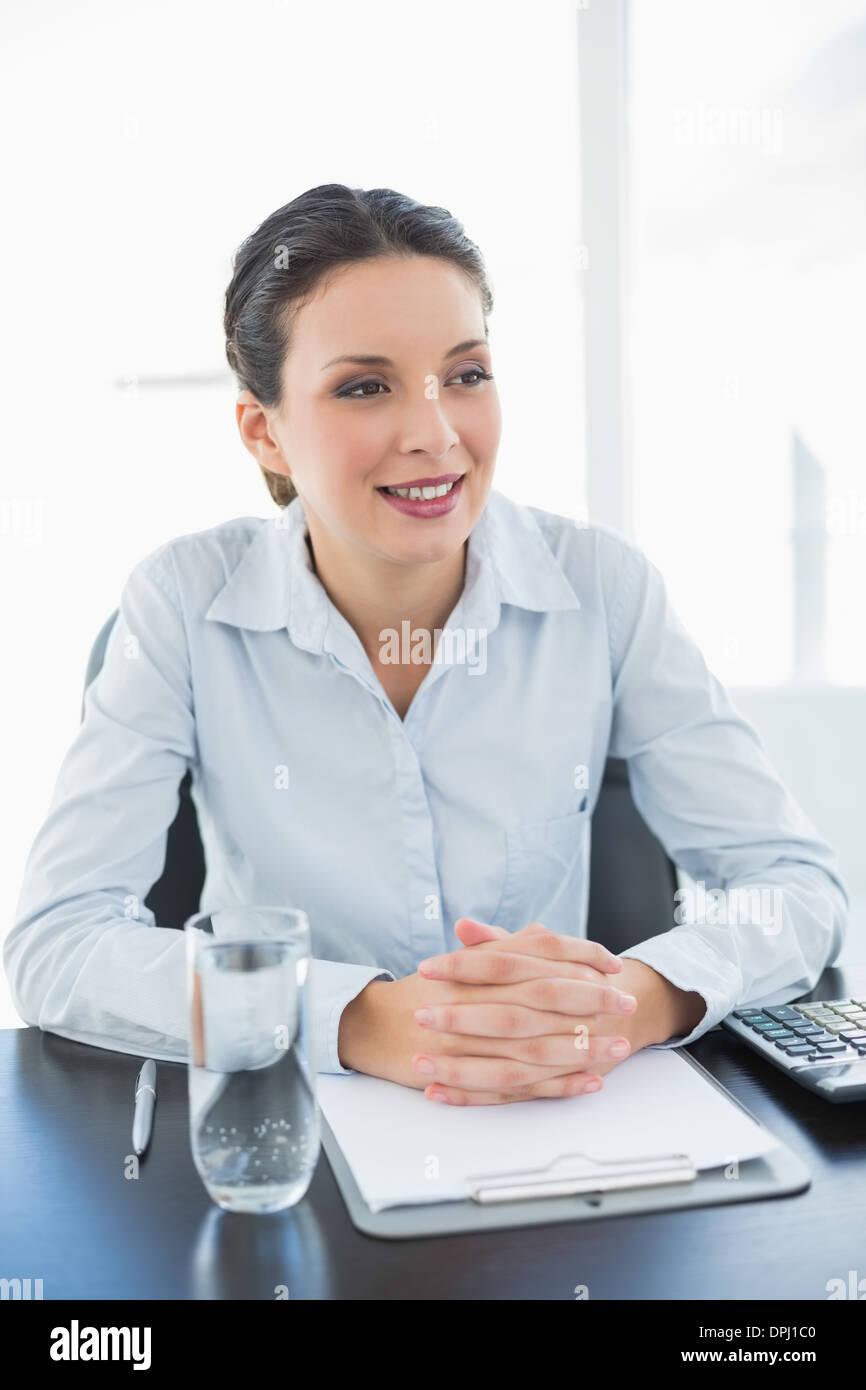 Stylish brunette businesswoman joining her hands and looking away - Stock Image