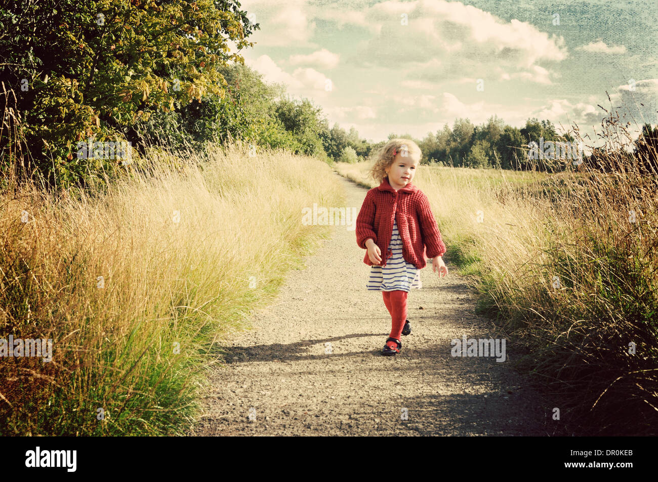 Little girl walking along path in countryside. - Stock Image