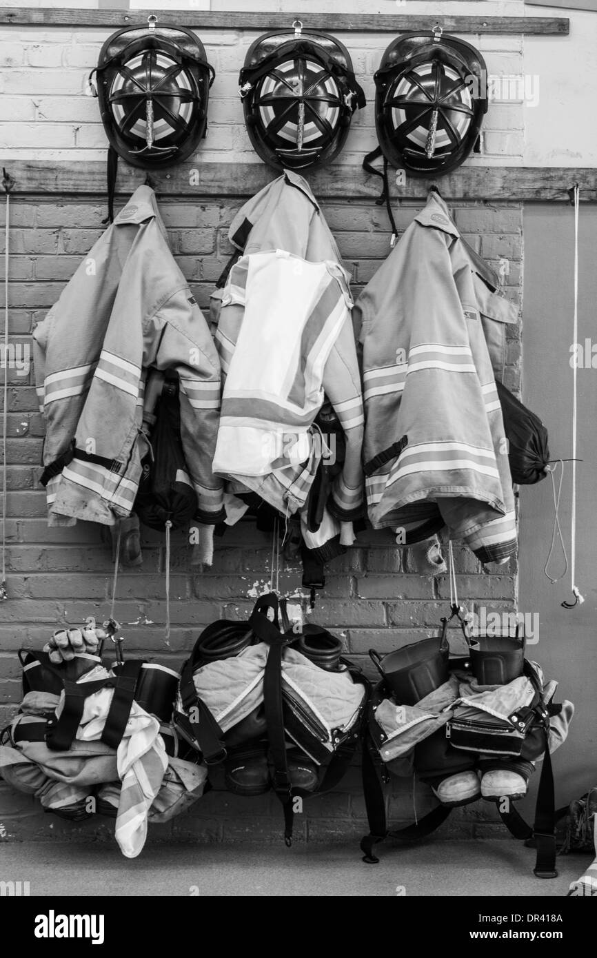 Three firefighter uniforms hanging on the station wall HDR - Stock Image