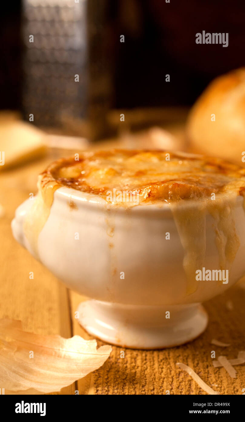 French onion soup with grated cheese and a round loaf of bread - Stock Image