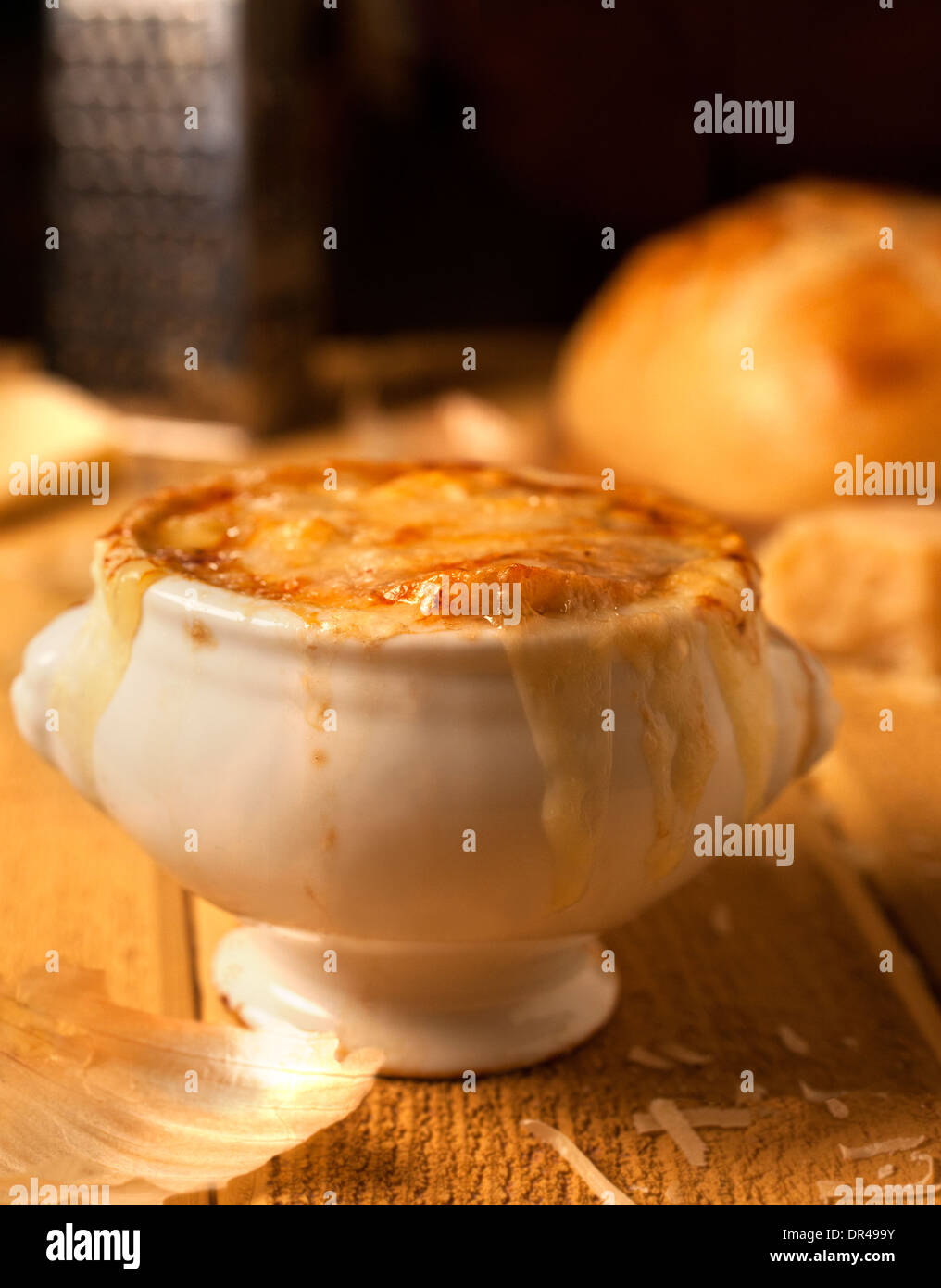 French onion soup with grated cheese and a round loaf of French bread - Stock Image