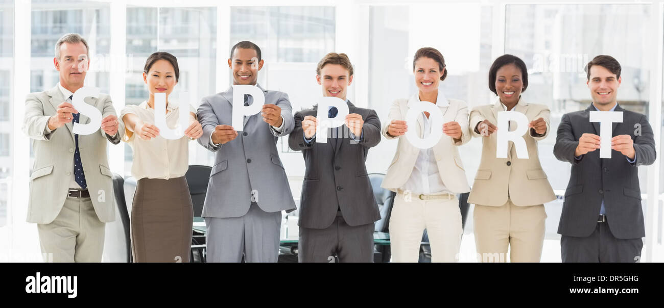 Diverse business team holding up letters spelling support - Stock Image