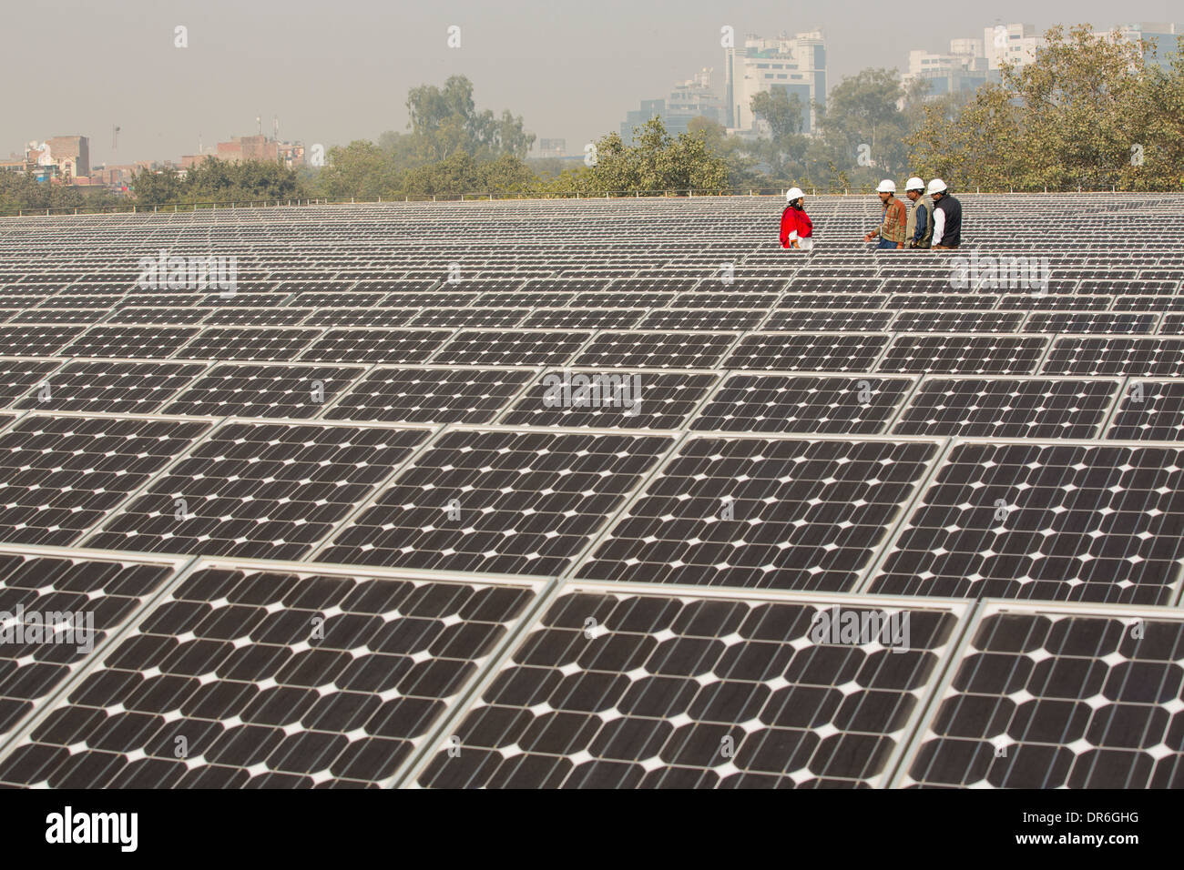 Workers at a 1 MW solar power station run by Tata power on the roof of an electricity company in Delhi, India. Stock Photo