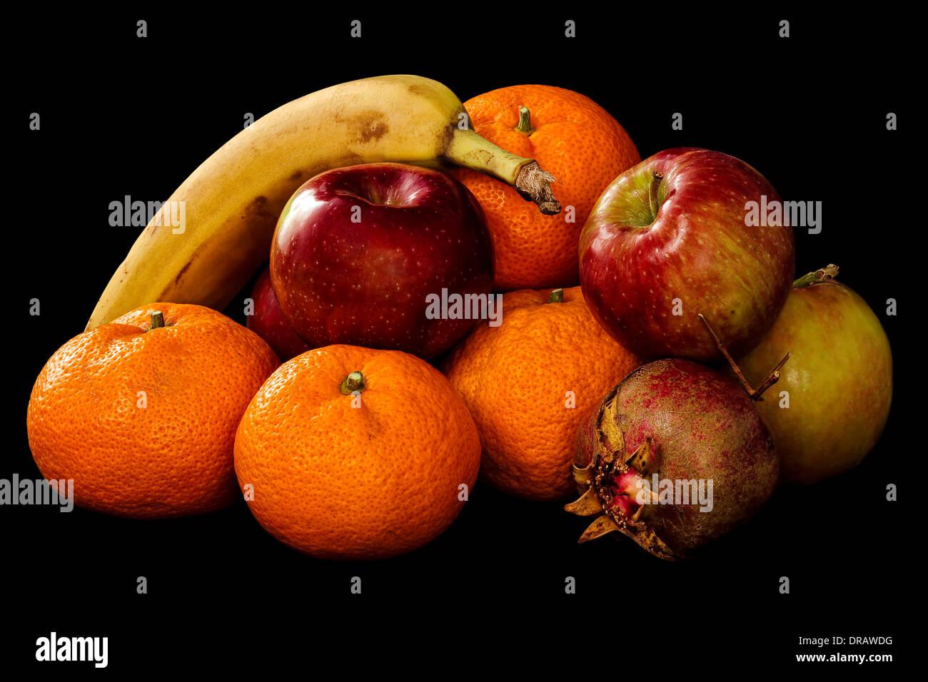 Mound of Fresh Fruit. Apples, Oranges, Banana, Pomegranate on a black background. - Stock Image