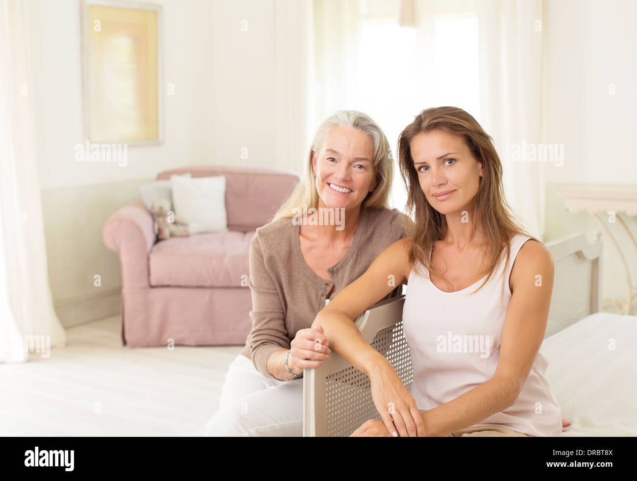 Mother and daughter smiling in bedroom - Stock Image