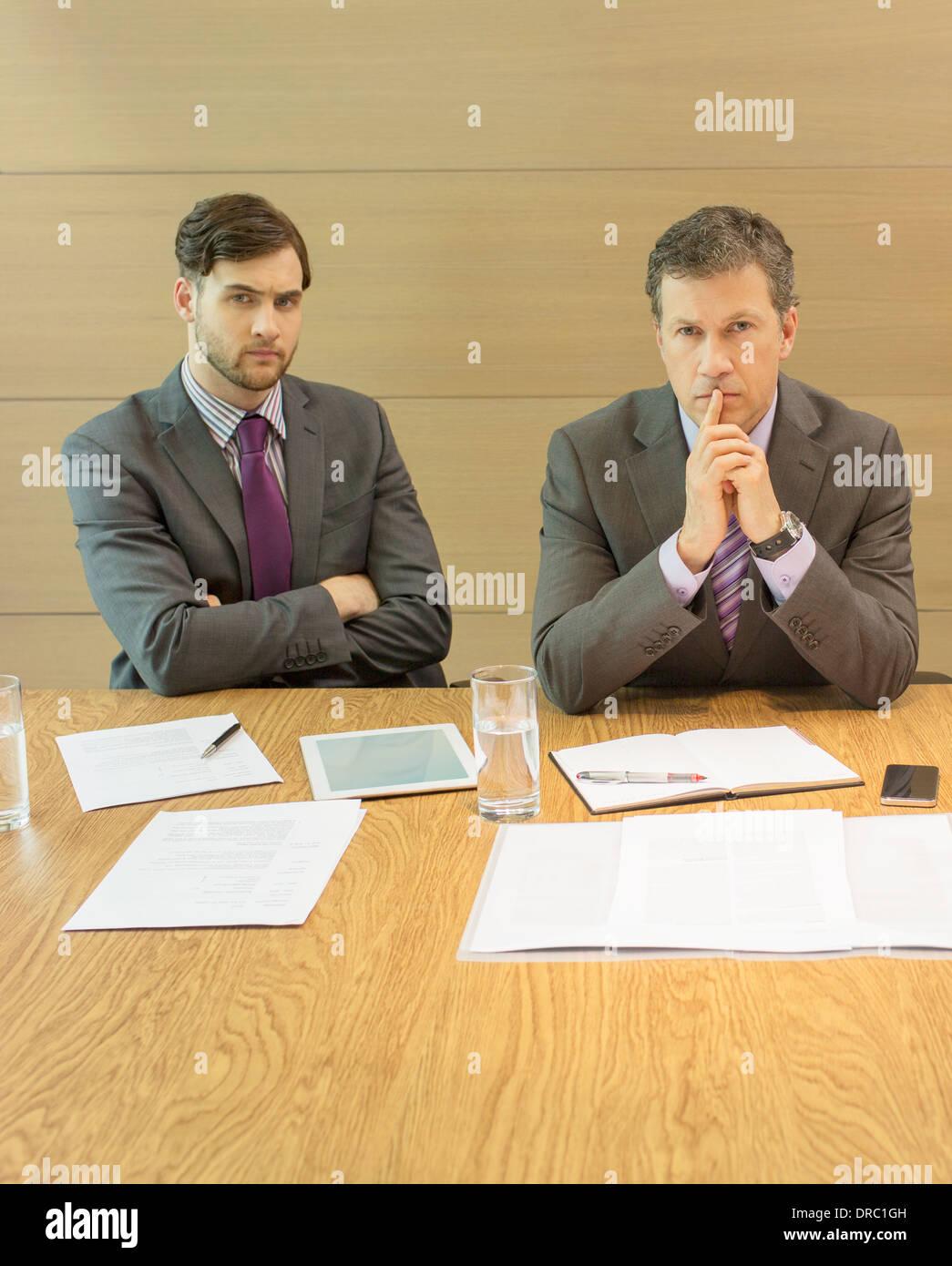 Businessmen sitting in meeting - Stock Image